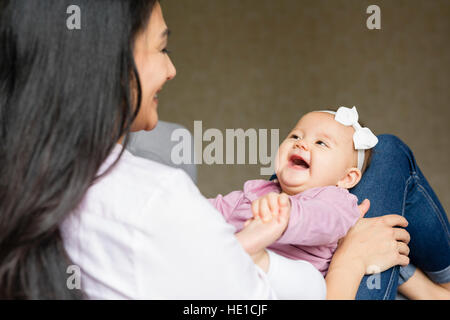 Mother is sitting with baby on an armchair - Stock Photo