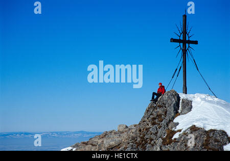 Woman, 22, at the summit cross, Mt. Steinerner Jaeger in the Pre-Alps near Reichraming in winter, Upper Austria, - Stock Photo