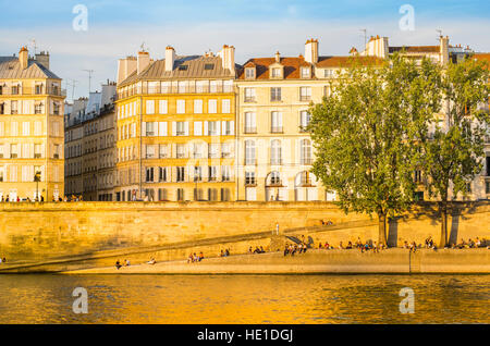 people enjoying sunset on the banks of river seine, quai d´orleans, ile saint louis - Stock Photo