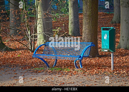 Blue park bench with a green trash can in autumn - Stock Photo