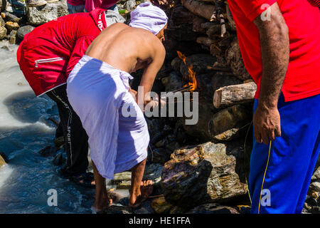 A man is lightning the fire at the funeral of a death body at the cremation ground on the bank of the river Kali - Stock Photo