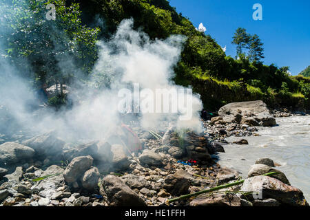 The fire of the funeral of a death body at the cremation ground on the bank of the river Kali Gandaki is producing - Stock Photo