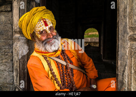 Portait of a Sadhu, holy man, sitting at a little shrine at Pashupatinath temple at the banks of Bagmati River - Stock Photo
