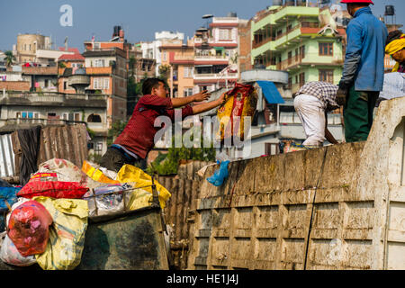 People are collecting garbage in the city, loading it on trucks and transporting it to a garbage dump outside the - Stock Photo
