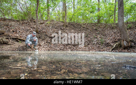 Tech. Sgt. Jonathan Eckley skims a creek-bed to look for mosquitos at Wright-Patterson Air Force Base, Ohio on April - Stock Photo