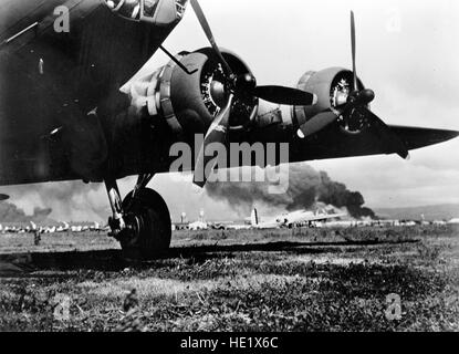 A photo taken at Hickam Air Base during the Japanese attack on 7 December 1941. A camouflaged Boeing B-17E Flying - Stock Photo