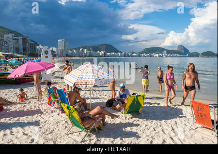 RIO DE JANEIRO - FEBRUARY 27, 2016: Beachgoers enjoy a tranquil late afternoon on Copacabana Beach as storm clouds - Stock Photo
