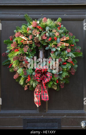 Christmas wreath on wooden door. Cotswolds, England - Stock Photo