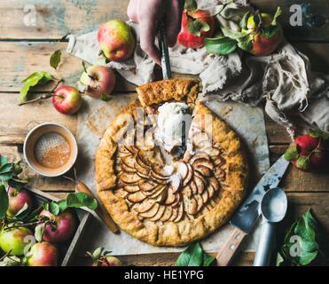 Man's hand holding piece of apple crostata pie - Stock Photo