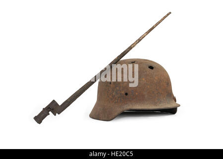 Rusty and holed German military helmet and Russian bayonet on white background - Stock Photo