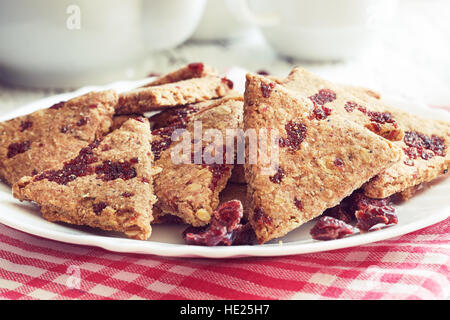 Whole wheat cookies with dried cranberries served on white plate - Stock Photo