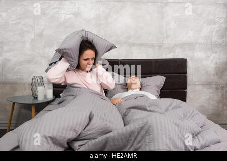 Annoyed wife blocking her ears by a pillow from noise of husband snoring in the bed in the bedroom in loft style - Stock Photo
