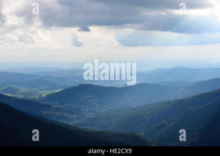 Distant forests and mountains with sunshine rays piercing through clouds - Stock Photo