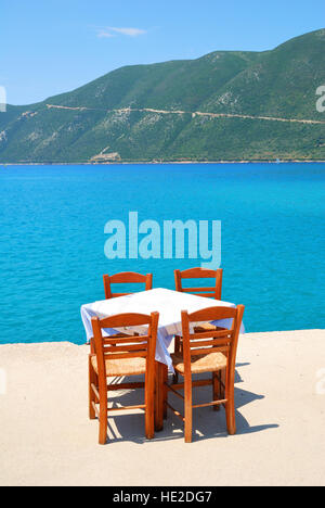 Dining table with chairs in a greek taverna with blue sea and green hills - Stock Photo