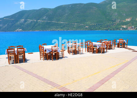 Dining tables with chairs in a greek harbour taverna with blue sea and green hills - Stock Photo