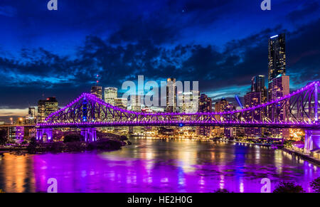 Vibrant night time panorama of Brisbane city with purple lights on Story Bridge, Australia - Stock Photo