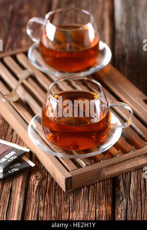 black tea in glass cup on wooden tray - Stock Photo