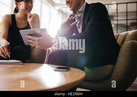 Cropped shot of business professionals having a meeting in office lobby using digital tablet. Business partners - Stock Photo