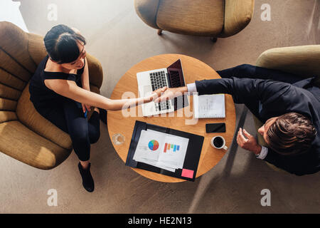 Top view of young business partners shaking hands on deal at office. Documents and laptop on table showing statistics - Stock Photo