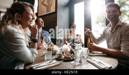 Group of friends enjoying an evening meal with wine at a restaurant. Happy young man and woman having dinner in - Stock Photo
