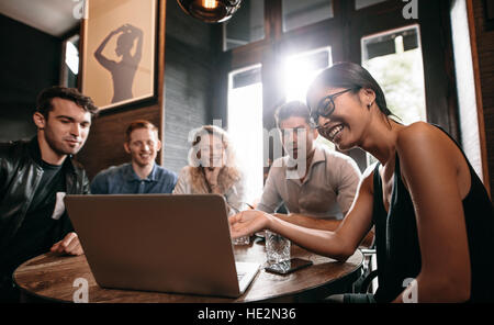Smiling young woman showing something on laptop to her friends. Group of young men and women at cafe looking at - Stock Photo