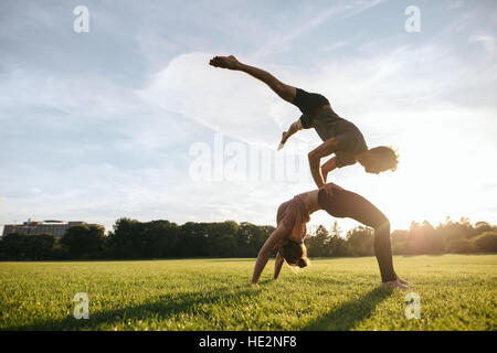 Healthy young couple doing pair yoga outdoor in park. Man doing handstand on torso of woman in park. - Stock Photo