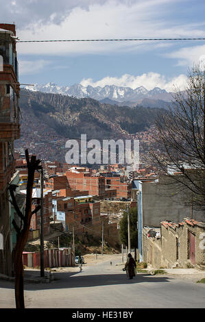 A silhoueete of a woman on the streets of La Paz, Bolivia, Illimani and snowy white mountain peaks of the Cordillera - Stock Photo