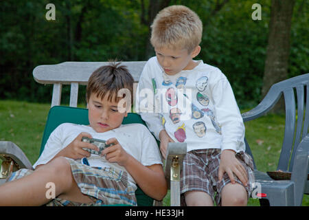Boys age 10 adsorbed playing electronic video game on cell phone. Clitherall Minnesota MN USA - Stock Photo