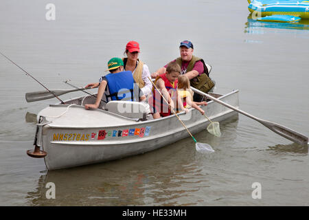 Family out fishing in rowboat while dad rows.  Clitherall Minnesota MN USA - Stock Photo