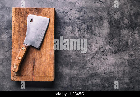 Butcher. Vintage butcher meat cleavers with cloth towel on dark concrete or wooden kitchen board. - Stock Photo