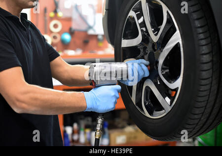 Mechanic changing a car tire in a workshop - Stock Photo
