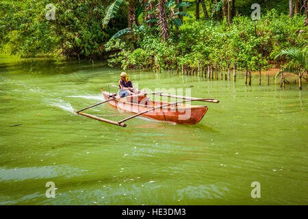 A Filipino man paddles his outrigger pontoon boat along the Loboc River on Bohol Island, Philippines, Southeast - Stock Photo