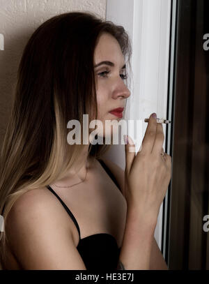 young beautiful woman smoking cigarette near window - Stock Photo