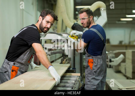 Young male workers work in a factory for the production of furniture - Stock Photo