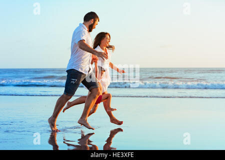 Happy family - father, mother, baby son hold hands, run together by water pool along sea surf on sunset black sand - Stock Photo