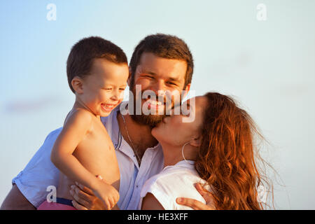 Face portrait of hugging beautiful family - happy mother, father holding baby son on hands walk with fun on sunset - Stock Photo