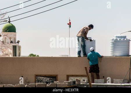 Oman Salalah 17.10.2016 People working in front of Mosque tower in ubar Dhofar mountain region Oman flag - Stock Photo