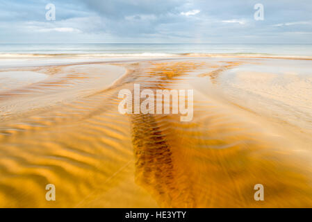 peat coloured water flowing over Traigh Garraidh (Garry beach) by Tolsta on east coat of Isle of Lewis, Outer hebrides, - Stock Photo