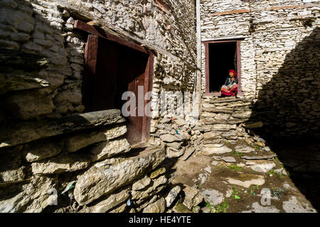 An old local farmers woman is sitting in the door of a stone house - Stock Photo
