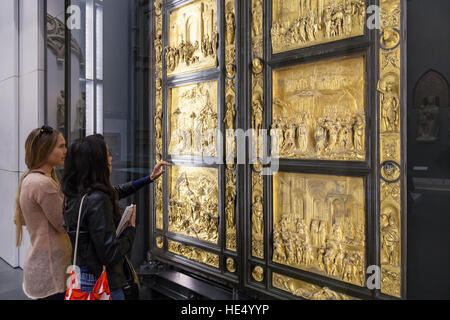 FLORENCE, ITALY - NOVEMBER 4, 2016: visitors near original gates in Museo dell Opera del Duomo (Museum of Works - Stock Photo
