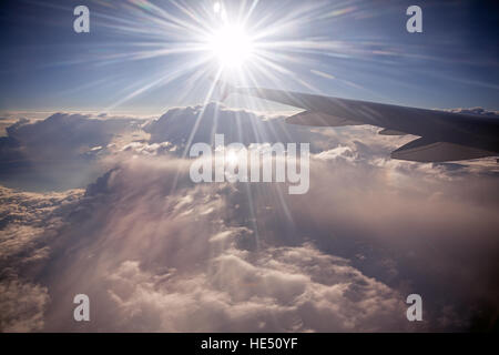 Wing of aircraft on the background of sunny rays and clouds. Fast aerial transport, traveling and voyage concept. - Stock Photo