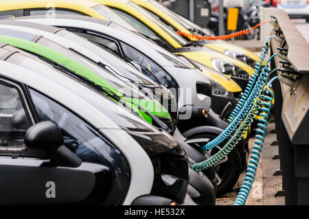 A number of Renault Twizy two seater city vehicles lined up at a charging station. - Stock Photo