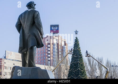 December 16, 2016 - Workers prepare the Christmas tree under the Lenin statue in main square of Donetsk city, Ukraine - Stock Photo