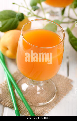 apricot juice in the glass with fruits around - Stock Photo