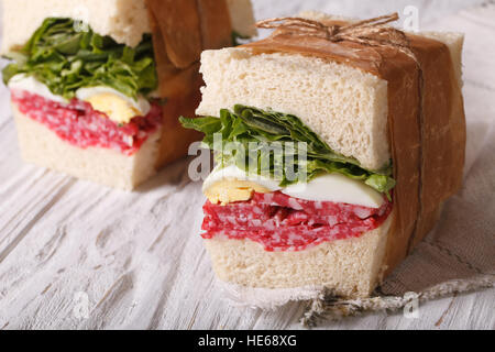 sandwiches with salami and egg wrapped in paper close-up on the table. horizontal - Stock Photo