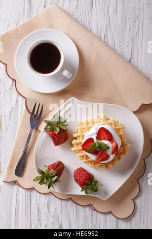 waffles with fresh strawberries, cream and coffee on a table. vertical top view - Stock Photo