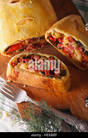 strudel with ham, cheese and spinach, close-up. Vertical, rustic - Stock Photo