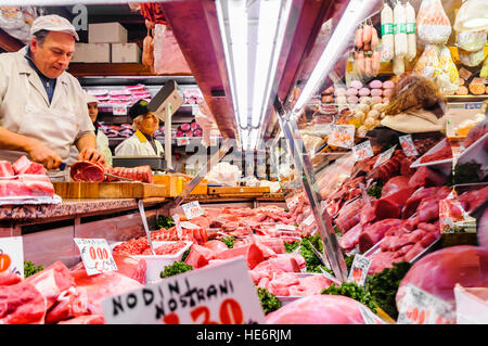 An Italian butcher prepares meat in his shop. - Stock Photo