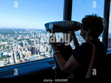 Tourist looks at view from CN Tower in Toronto - Stock Photo