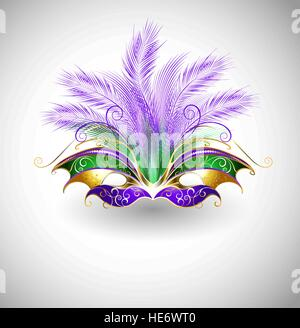 bright mask with purple and green feathers, decorated with gold pattern on a light background - Stock Photo